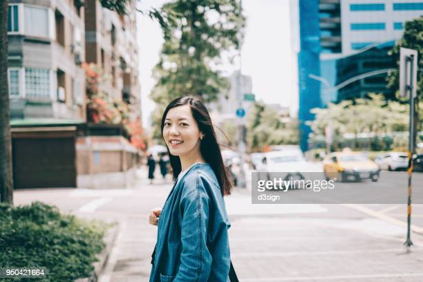 beautiful asian female traveller smiling and walking in city street - 肩ごしに見る ストックフォトと画像