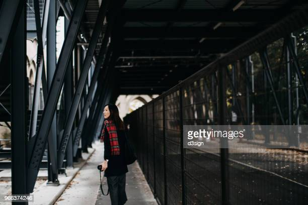 beautiful asian female traveller with camera strolling and exploring in the city - 見渡す ストックフォトと画像
