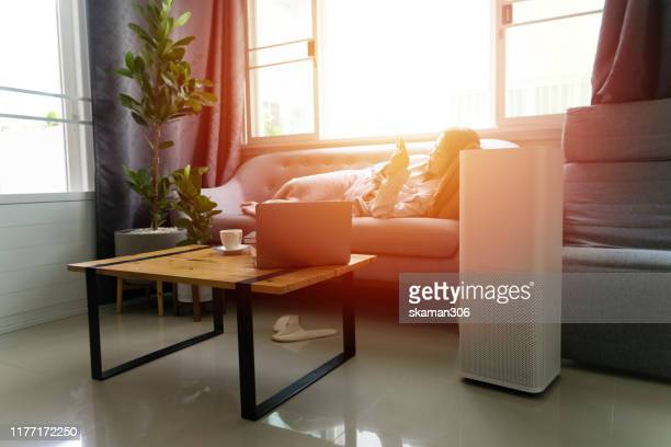 beautiful asian girl female feeling fresh and relax on cozy sofa with air purifier machine - air respirator mask stock pictures, royalty-free photos & images