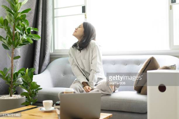 beautiful asian girl female happy and relax on cozy sofa with air purifier machine - air respirator mask stock pictures, royalty-free photos & images
