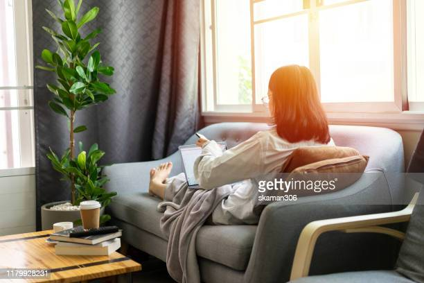 beautiful asian girl female start up working with laptop computer on cozy sofa with air purifier machine - air respirator mask stock pictures, royalty-free photos & images