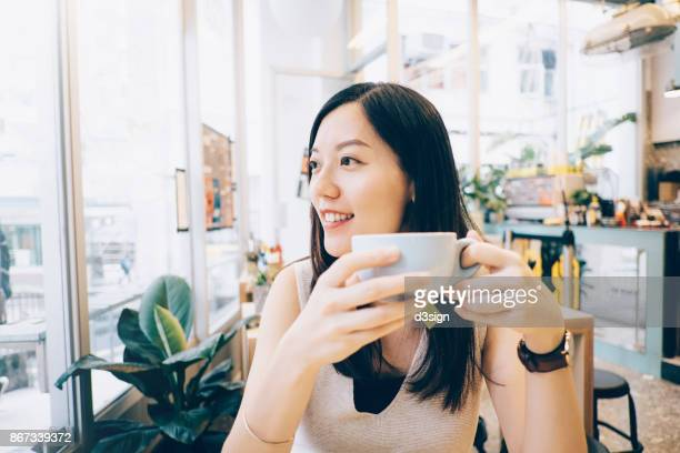 Beautiful Asian girl relaxing and having coffee in cafe