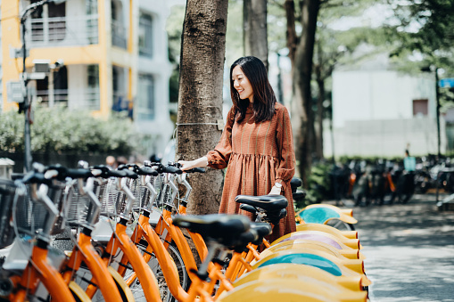 Beautiful Asian girl renting shared bicycle in city centre - gettyimageskorea