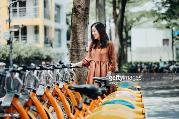 Beautiful Asian girl renting shared bicycle in city centre