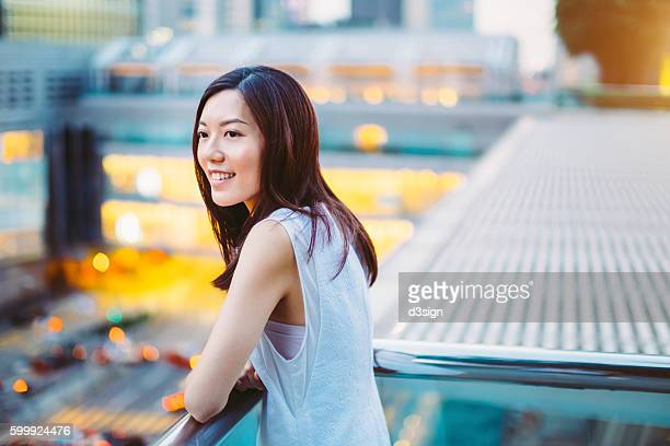 Beautiful Asian girl standing on the balcony of the roof top terrace of a building looking far away, with Hong Kong cityscape as the background.