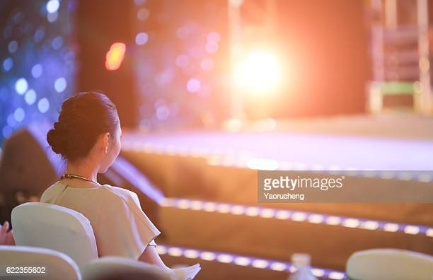 A beautiful Asian girl thinking in front of the stage,with colorful lighting