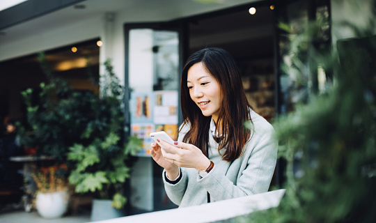 Beautiful Asian lady using smartphone and relaxing in outdoor cafe - gettyimageskorea