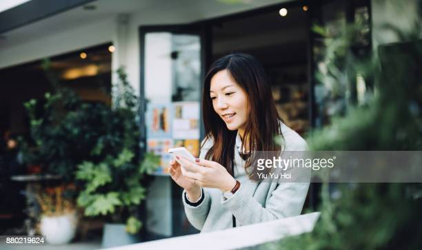 beautiful asian lady using smartphone and relaxing in outdoor cafe - オープンカフェ ストックフォトと画像