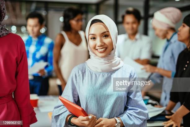 mooie aziatische millennial ondernemer die hijab draagt en digitale tablet in bureau na covid-19 pandemie gebruikt - zuidoost aziatische etniciteit stockfoto's en -beelden