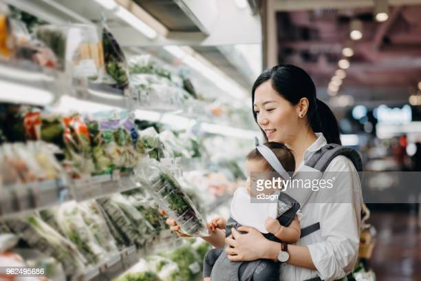 Beautiful Asian mother carrying cute baby girl shopping for organic fresh vegetables in grocery store