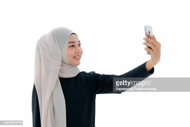 beautiful asian muslim woman holding mobile or smart phone and making selfie on white background - 宗教的なベール ストックフォトと画像