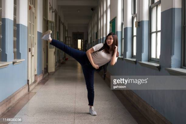 美しいアジアの学生がヴィンテージ大学の廊下でサイドキックを実演 - kicking ストックフォトと画像