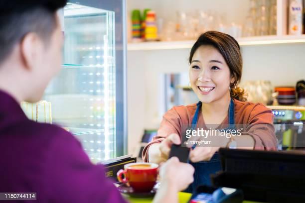 mooie aziatische serveerster ontvangende creditcard betaling van de klant in café. - klanten georiënteerd stockfoto's en -beelden