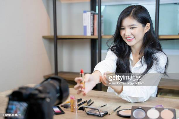 beautiful asian woman blogger is showing how to make up and use cosmetics. in front of the camera to recording vlog video live streaming at home.business online. - crash site stock pictures, royalty-free photos & images