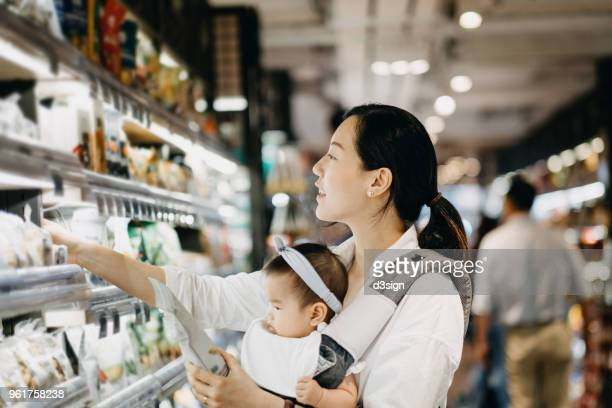 beautiful asian woman carrying cute baby girl shopping for organic green marketing products in grocery store - groceries stock pictures, royalty-free photos & images