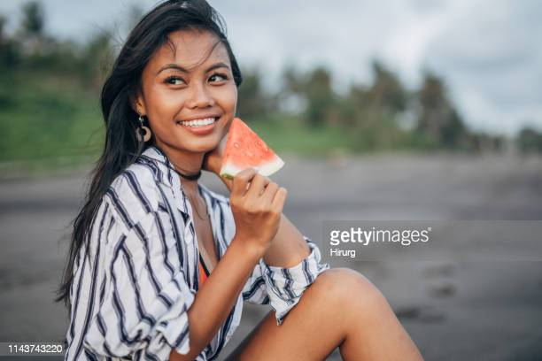 beautiful asian woman eating watermelon - indonesian culture stock pictures, royalty-free photos & images
