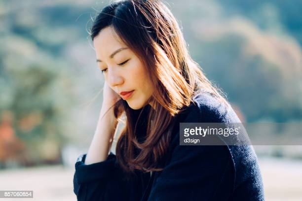 beautiful asian woman enjoying the fresh air and the warmth of sunshine in park - luogo d'interesse locale foto e immagini stock
