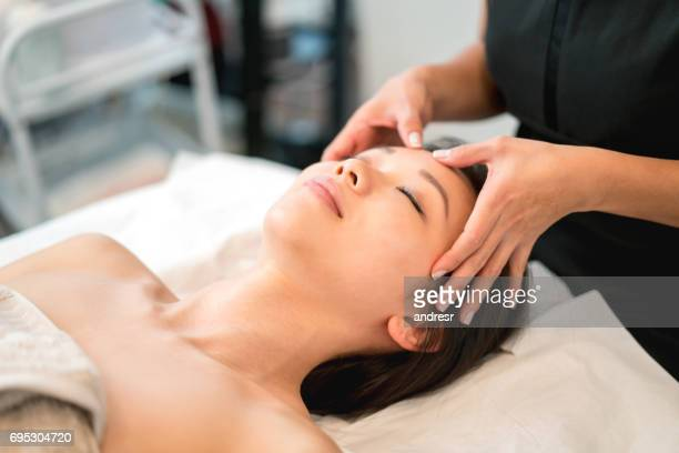 beautiful asian woman getting a face massage at the spa - spa treatment stock pictures, royalty-free photos & images