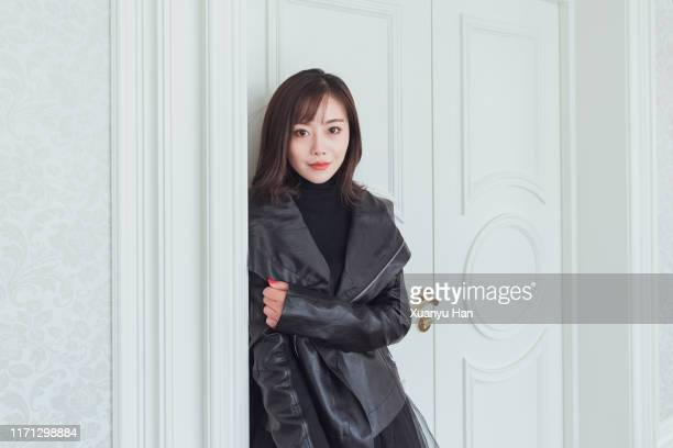 beautiful asian woman in leather jacket standing in front of the door - leather jacket stock pictures, royalty-free photos & images