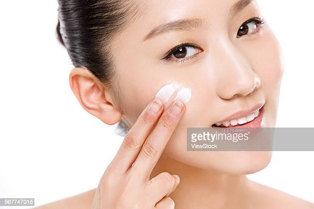 Beautiful oriental woman in painted skin care products