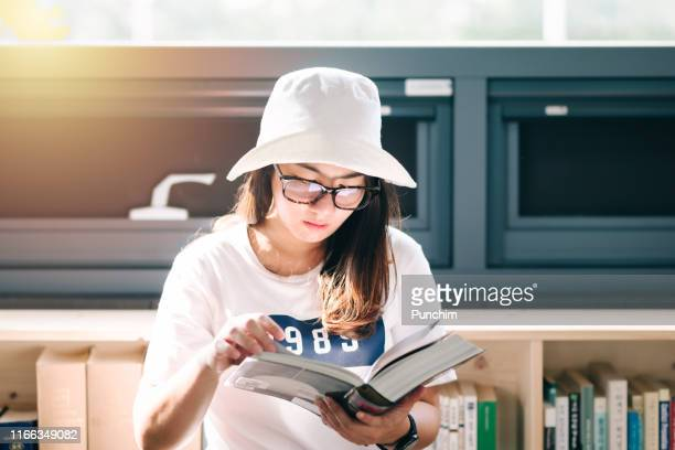 beautiful asian woman is reading a book in the library. to prepare for the exam - korean teen stock pictures, royalty-free photos & images