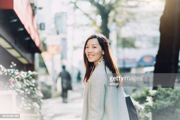 beautiful asian woman looking back with smile on the street - ビジネスウェア ストックフォトと画像