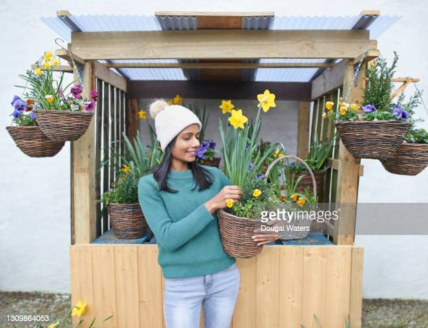 beautiful asian woman on flower stall carrying potted daffodils. - headwear stock pictures, royalty-free photos & images