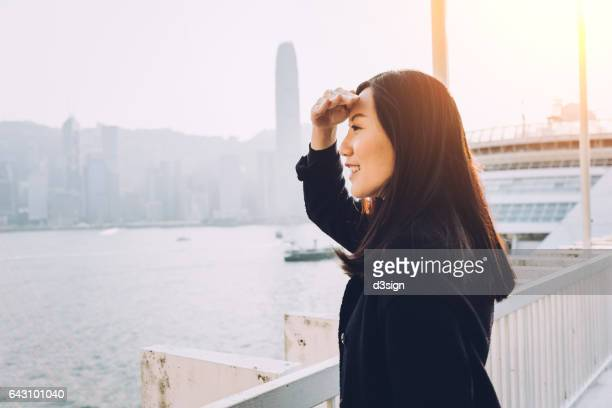 Beautiful Asian woman overlooking cityscape from roof top terrace