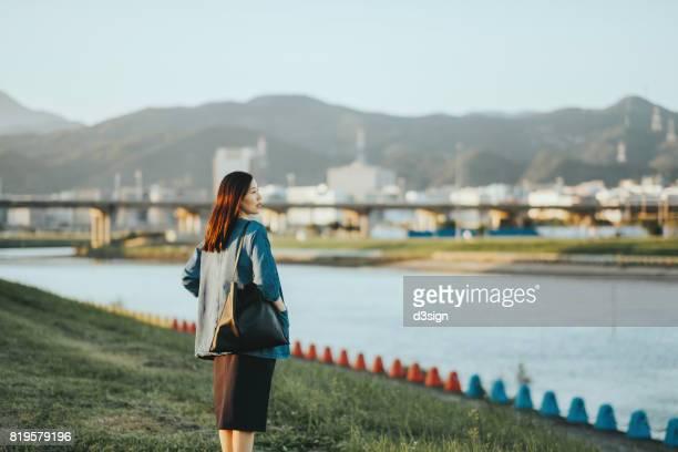 Beautiful Asian woman relaxing and enjoying the calmness in park