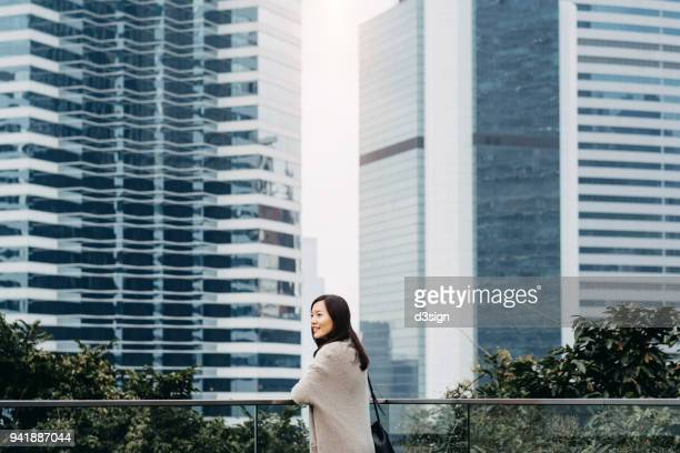Beautiful Asian woman relaxing and enjoying the city view over the sky garden