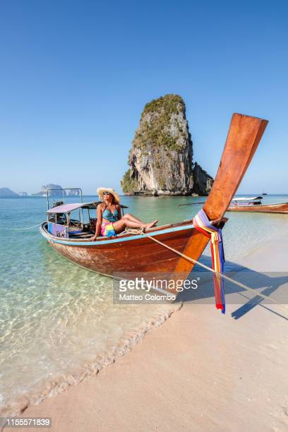 beautiful asian woman sitting on boat, railay, thailand - asiatisches langboot stock-fotos und bilder
