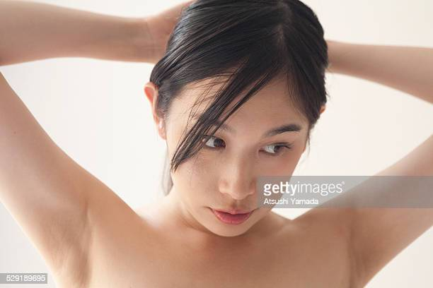 Beautiful asian woman tying her hair