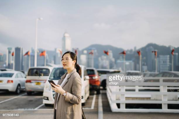 Beautiful Asian woman using mobile phone in outdoor car park against cityscape of Hong Kong