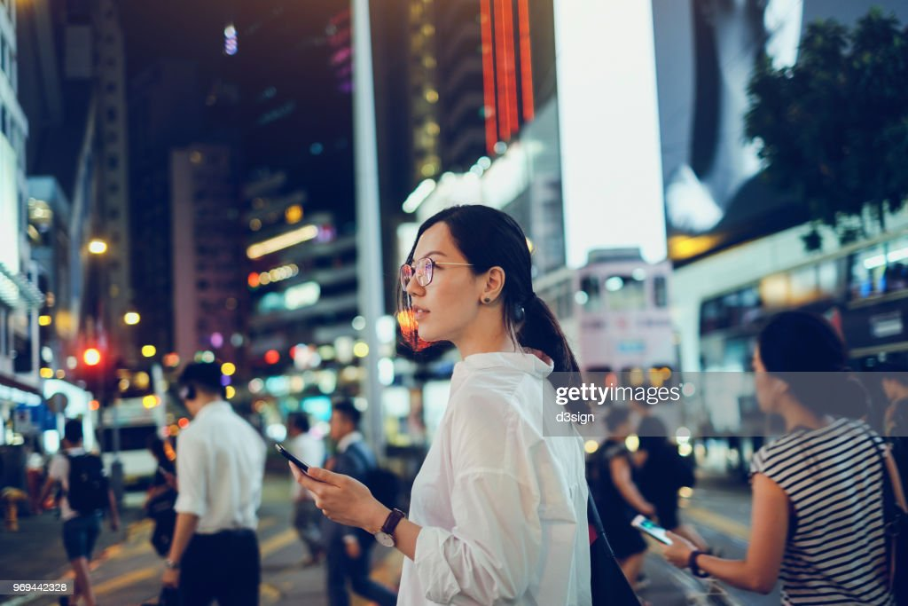 Beautiful Asian woman using mobile phone while crossing road in busy downtown city street at night : Foto stock