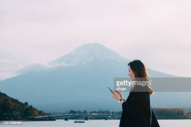 beautiful asian woman using smartphone against mt fuji and lake kawaguchiko - satoyama scenery stock pictures, royalty-free photos & images
