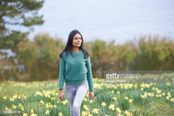 beautiful asian woman walking through daffodil field in countryside. - dougal waters stock pictures, royalty-free photos & images