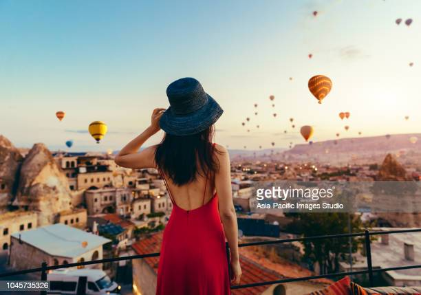 beautiful asian woman watching  colorful hot air balloons flying over the valley at cappadocia, turkey. turkey cappadocia fairytale scenery of mountains. - balloon ride stock pictures, royalty-free photos & images