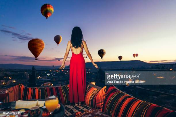 beautiful asian woman watching colorful hot air balloons flying over the valley at cappadocia, turkey.turkey cappadocia fairytale scenery of mountains.. turkey cappadocia fairytale scenery of mountains. - cappadocia stock pictures, royalty-free photos & images