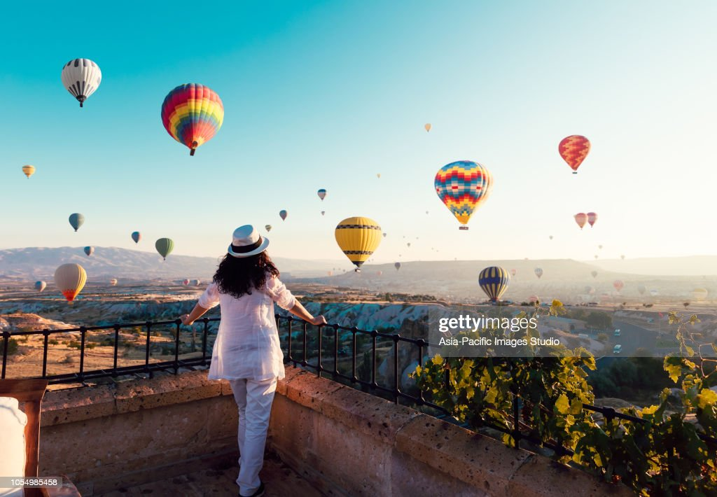 Beautiful asian woman watching colorful hot air balloons flying over the valley at Cappadocia, Turkey.Turkey Cappadocia fairytale scenery of mountains. Turkey Cappadocia fairytale scenery of mountains. : Stock Photo