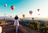 Beautiful asian woman watching colorful hot air balloons flying over the valley at Cappadocia, Turkey.Turkey Cappadocia fairytale scenery of mountains. Turkey Cappadocia fairytale scenery of mountains.