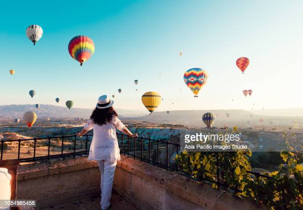 beautiful asian woman watching colorful hot air balloons flying over the valley at cappadocia, turkey.turkey cappadocia fairytale scenery of mountains. turkey cappadocia fairytale scenery of mountains. - viaggio foto e immagini stock