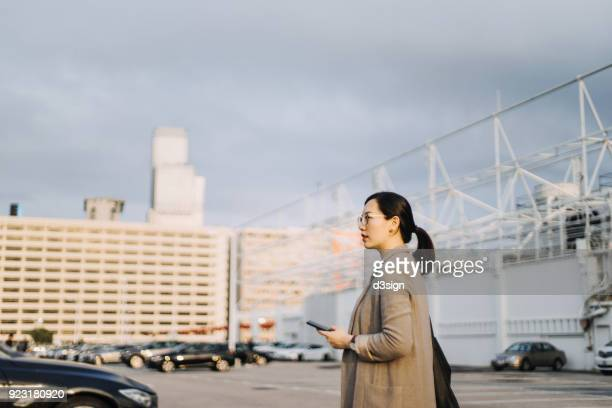 Beautiful Asian woman with mobile phone walking to her car in outdoor car park against urban cityscape
