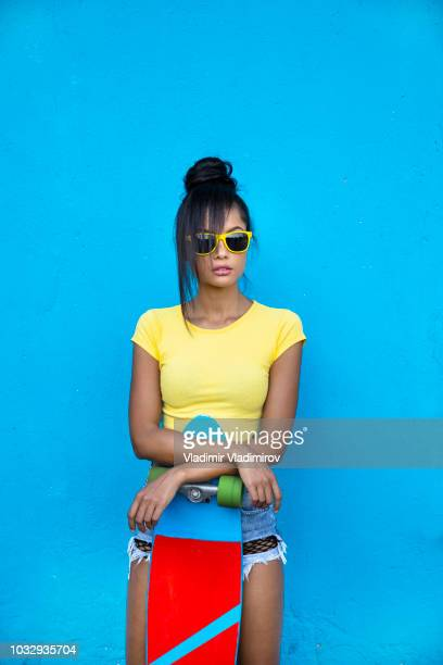 beautiful asian woman with skateboard in front of blue background - funky foto e immagini stock
