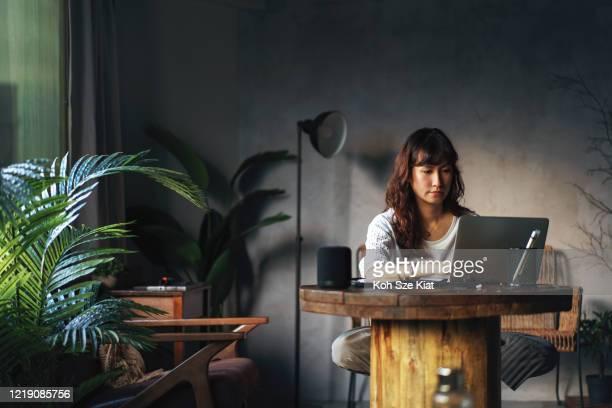 美しいアジアの女性は、支援のためのスマートスピーカーで自宅から働く - 検索エンジン ストックフォトと画像