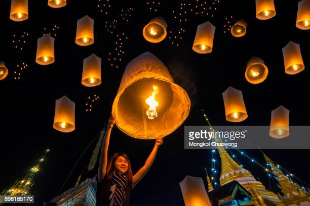 beautiful asian women release sky lanterns to worship buddha's relics in yi peng or yee peng festival at wat jongklang temple - wat jongkham temple in mae hong son near chiang mai, thailand. - mois de mai photos et images de collection