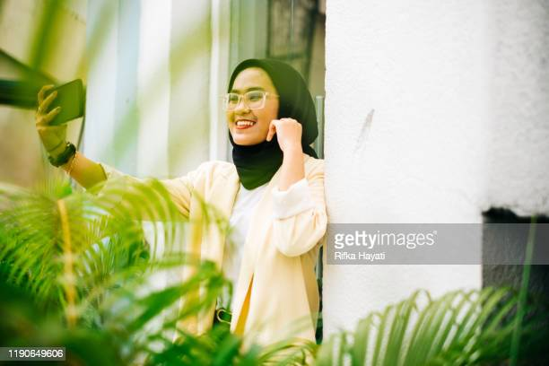 beautiful asian women taking selfie with mobile phone - rifka hayati stock pictures, royalty-free photos & images