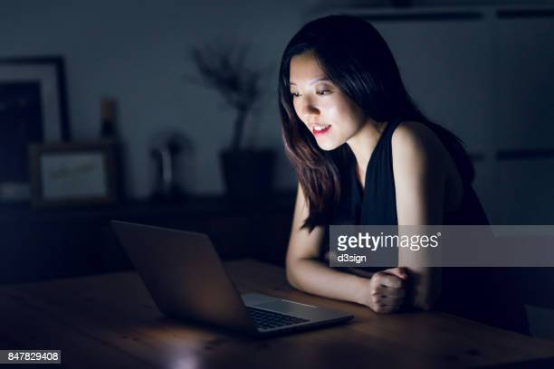 beautiful asian young lady surfing the net with notebook till late night at home - internet dating stock pictures, royalty-free photos & images