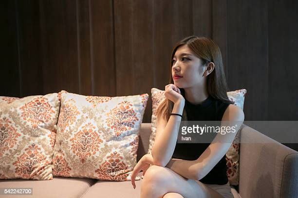 A Beautiful Asian Young Woman Sitting on a Soft and Looking Right and Thinking