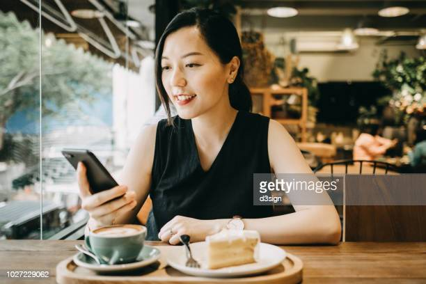 beautiful asian young woman text messaging on mobile phone in coffee shop - カフェ ストックフォトと画像