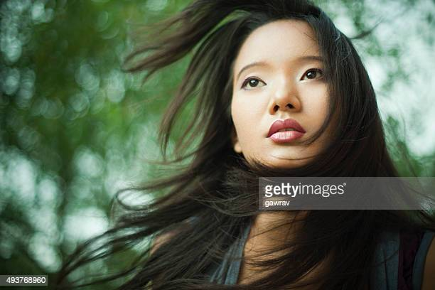 Beautiful Asian young woman with flying hair in nature.